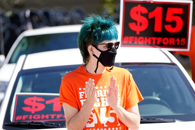 Cristian Cardona, an employee at a McDonald's, attends a rally for a $15 an hour minimum wage Tuesday, Feb. 16, 2021, in Orlando, Fla. (AP Photo/John Raoux)