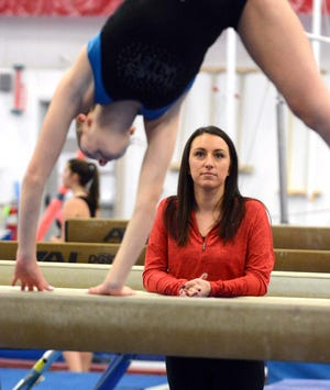 NFA gymnastics coach Cindy Briggs watches Michaela Ryan work out on the beam last season at Thames Valley Gymnastics in Franklin.