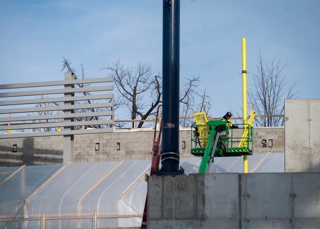 Workers install the right field foul pole at Polar Park on Wednesday.