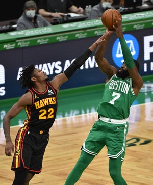 Celtics guard Jaylen Brown forces up a shot through the defense of Hawks guard Cam Reddish during the first half Wednesday night at TD Garden.