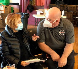 Clinton Fire Chief Michael Lutes speaks with resident Maria Kobus during one of two COVID-19 vaccination clinics in Clinton for the oldest residents in town. Last week, 60 seniors were vaccinated in the auditorium at Clinton Town Hall. This week, there were 80 vaccinated, including 12 home visits, according to Senior Center Director Debra Goodsell.