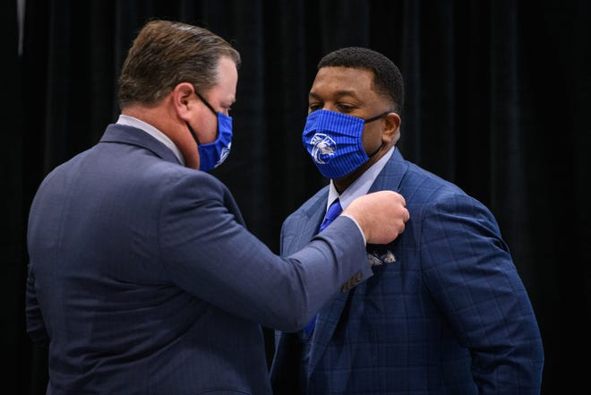 Trustee Stuart Augustine, left, pins a Fayetteville State pin onto Darrell Allison during a press conference at Fayetteville State University on Feb. 18.
