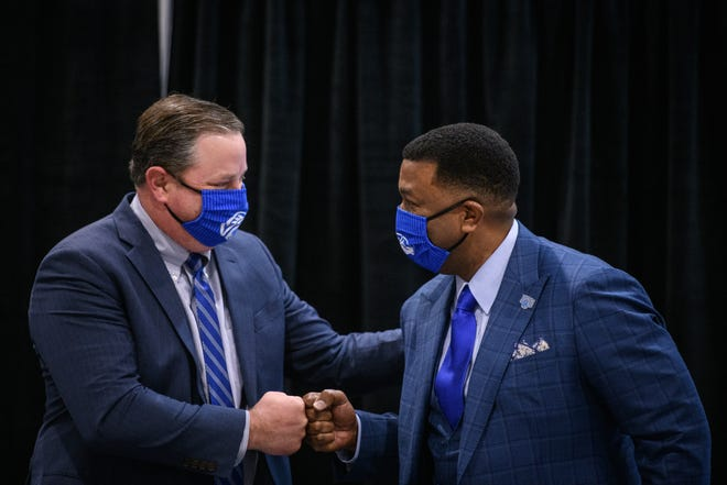 Stuart Augustine, left, chairman of the Fayetteville State University board of trustees, fist bumps Darrell Allison during a press conference Feb. 18.