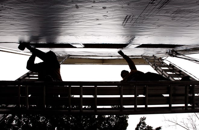 Construction workers fasten insulation to the outside of a house for a super insulation pilot project designed to conserve energy and control heating and cooling costs for the homeowner.