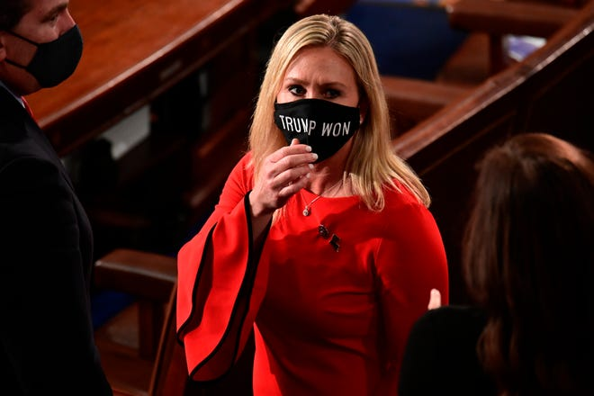 """Rep. Marjorie Taylor Greene, R-Ga., wears a """"Trump Won"""" face mask as she arrives on the floor of the House to take her oath of office on opening day of the 117th Congress at the U.S. Capitol in Washington on Jan. 3."""