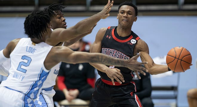 Northeastern point guard Tyson Walker, here being defended in a game against North Carolina in February, announced Saturday that he'll transfer to Michigan State.