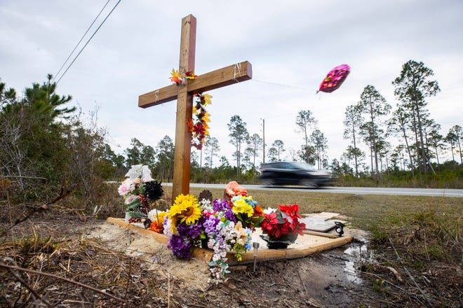 A memorial cross with flowers and balloons marks the spot where four people were killed in an auto accident on Sept. 15, 2020, on State 388.