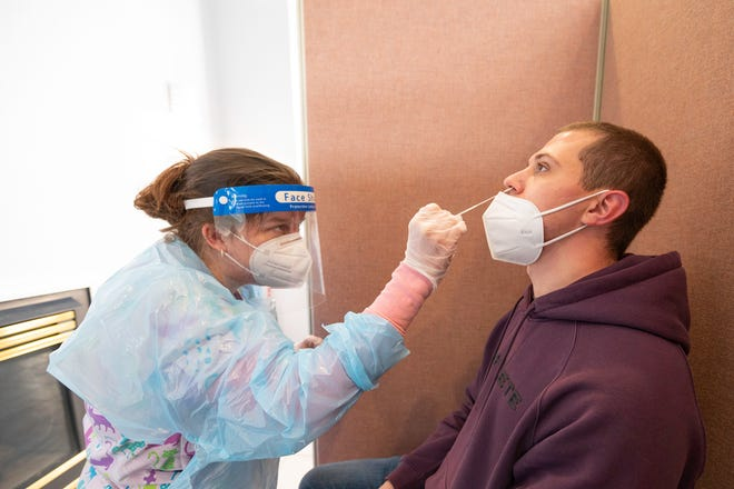 Amy Sams, left, administers a COVID-19 test on Josh Frick at the Colorado State University Pueblo campus testing site on Thursday February 18, 2021.