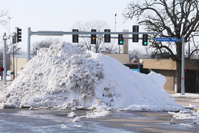After clearing the Baptist Health Medical Plaza parking lot, snow was piled up to melt and drain away, Thursday, Feb. 18.