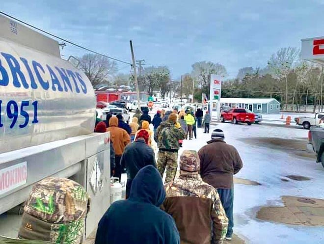A long queue forms at Pearman Oil & Gas LP Inc. at 101 South U.S. Highway 77 as local residents seek propane cylinder refills. The company stayed open late to service customers in need.