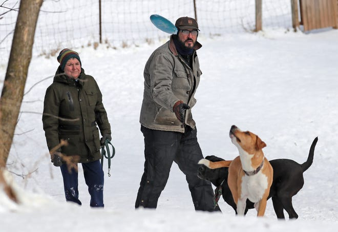Jackie Duscher, left, of Appleton and Dean Chagares of Wrightstown play with their dogs Nysa and Mobey at the Outagamie County North Dog Park on Thursday, February 18, 2021, in Appleton, Wis. The park will close in March.