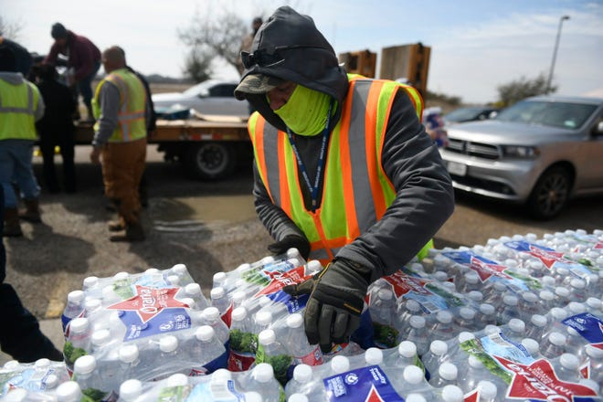 A volunteer helps stack water bottles that were delivered to seniors on Thursday, Feb. 18, 2021 as part of Corpus Christi's Meals on Wheels program.