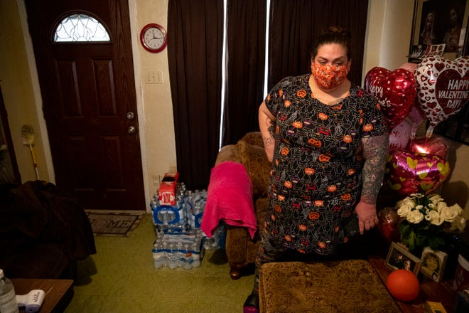 Natalie Cruz stands in her living room Thursday next to packs of drinking water. Her family had to shut off the home's water after a pipe broke during the freezing temperatures Monday. Cruz has been unable to find a plumber to come out to her home to fix the broken pipe.