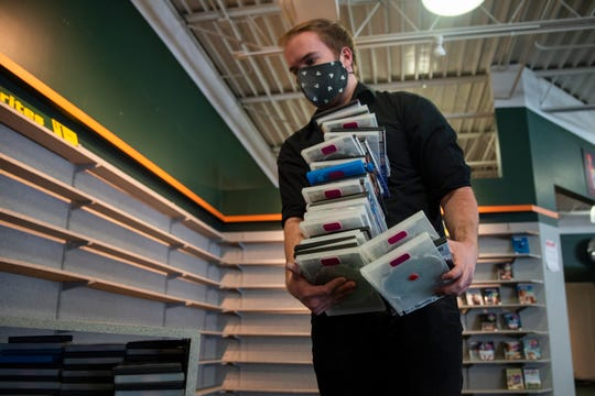 Family Video manager Cameron Redshaw gathers DVDs from shelves on Feb. 17, 2021, in West Des Moines at the company's last location in central Iowa. The Illinois-based company announced in early January that it would close all remaining locations. Co-workers and movie discussions are what he'll miss most, Redshaw said.