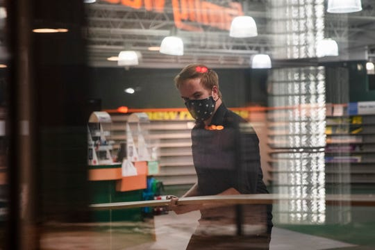 Family Video manager Cameron Redshaw dissembles shelves on Feb. 17, 2021 in West Des Moines at the company's last location in central Iowa.