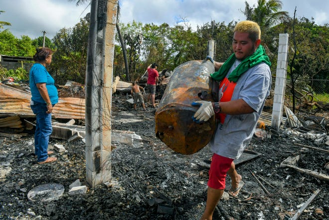 Benjamin Santos, 29, hauls out a burnt water heater from the charred rubble of a home that once housed his family of seven in Astumbo, Dededo on Thursday, Feb. 18, 2021. The family was able to escape a blaze, which destroyed the mostly wood and tin structure, the afternoon before.