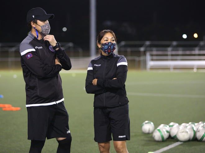 Newly appointed Masakåda assistant coach Rhoda Bamba, right, observes players with Guam Women's National Team Head Coach Sang Hoon Kim, left, during warm-up ahead of a recent training session at the Guam Football Association National Training Center.