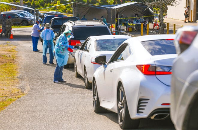 Health professionals conduct free COVID-19 tests for island residents, during a drive-through clinic hosted by the Department of Public Health and Social Services, at the Yona gymnasium on Thursday, Feb. 18, 2021.