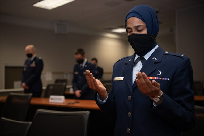 1st Lt. Saleha Jabeen, a graduate of Basic Chaplain Course Class 21A, raises her hands in prayer during a group prayer at the start of the graduation ceremony Feb. 5, 2021, at the Ira C. Eaker Center for Leadership Development on Maxwell Air Force Base, Ala. Jabeen, a native of India, is the first female Muslim chaplain to serve in the US military.