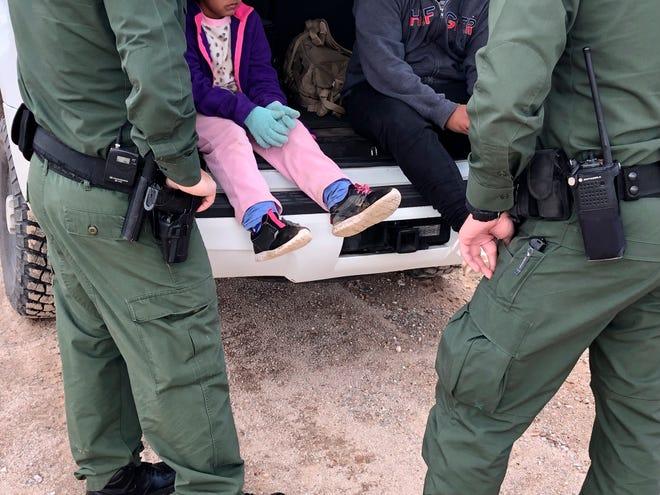 Fotografía del 22 de febrero donde aparecen dos agentes de la Patrulla Fronteriza mientras atienden a unos niños en la frontera de Arizona con México.