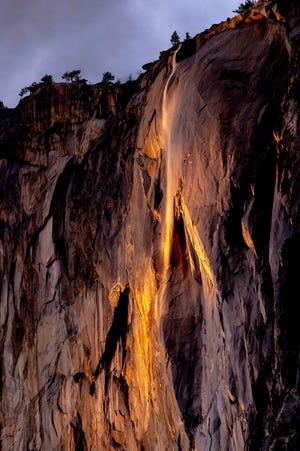 A narrow slit of light from the setting sun illuminates Horsetail Fall in Yosemite National Park on Tuesday, February 16, 2021.