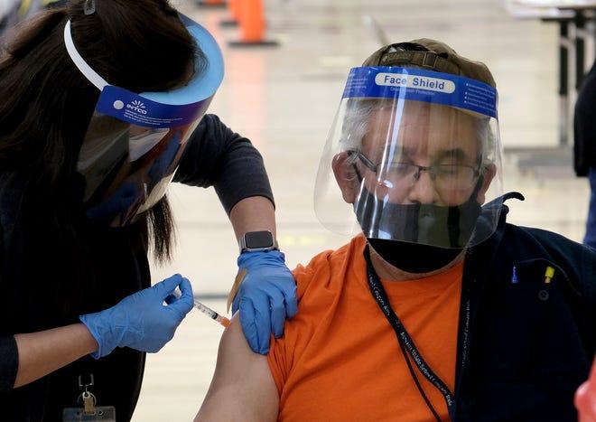 Raymundo Armagnac, qui travaille à l'école élémentaire Denker à Gardena près de Los Angeles, reçoit sa première dose du vaccin Moderna COVID-19 mercredi au Roybal Learning Center.