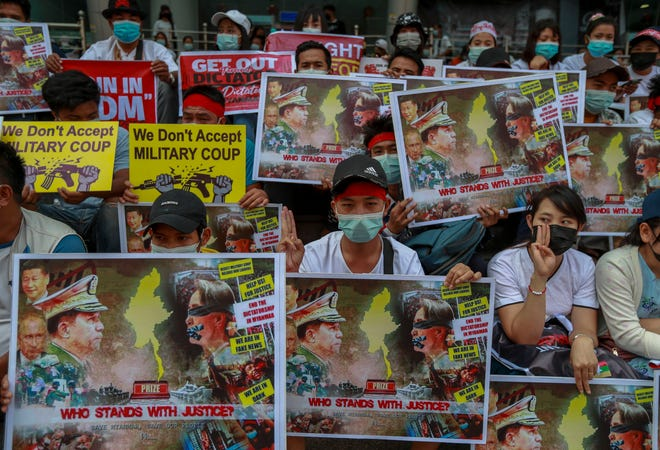 Protesters hold pictures of Senior Gen. Min Aung Hlaing and ousted leader Aung San Suu Kyi in Yangon, Myanmar, on Feb. 18, 2021.