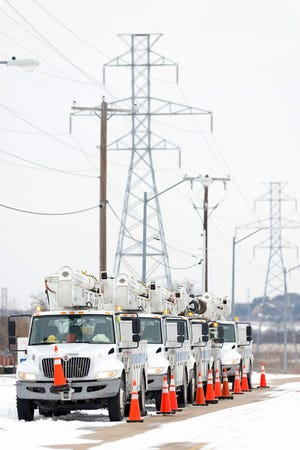 Electric service trucks on Feb. 16, 2021, in Fort Worth, Texas.