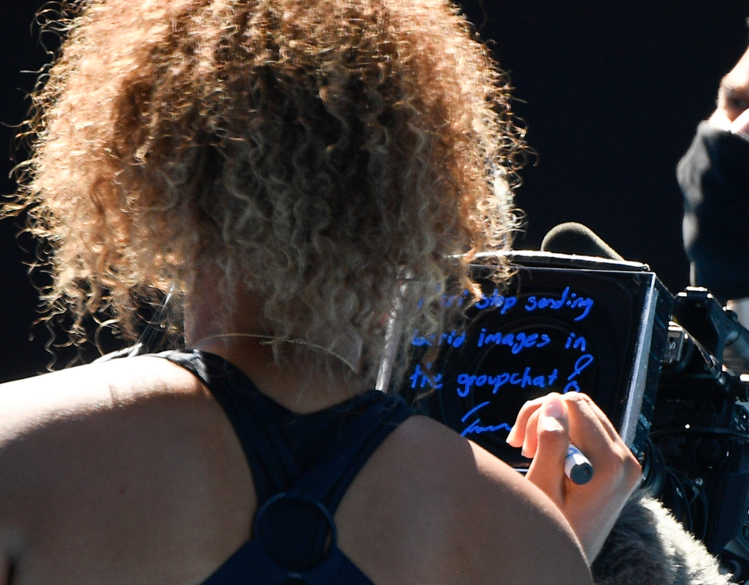 Japan's Naomi Osaka writes a massage on a TV screen as she leaves Rod Laver Arena after defeating United States' Serena Williams in their semifinal match at the Australian Open tennis championship in Melbourne, Australia, Thursday, Feb. 18, 2021.