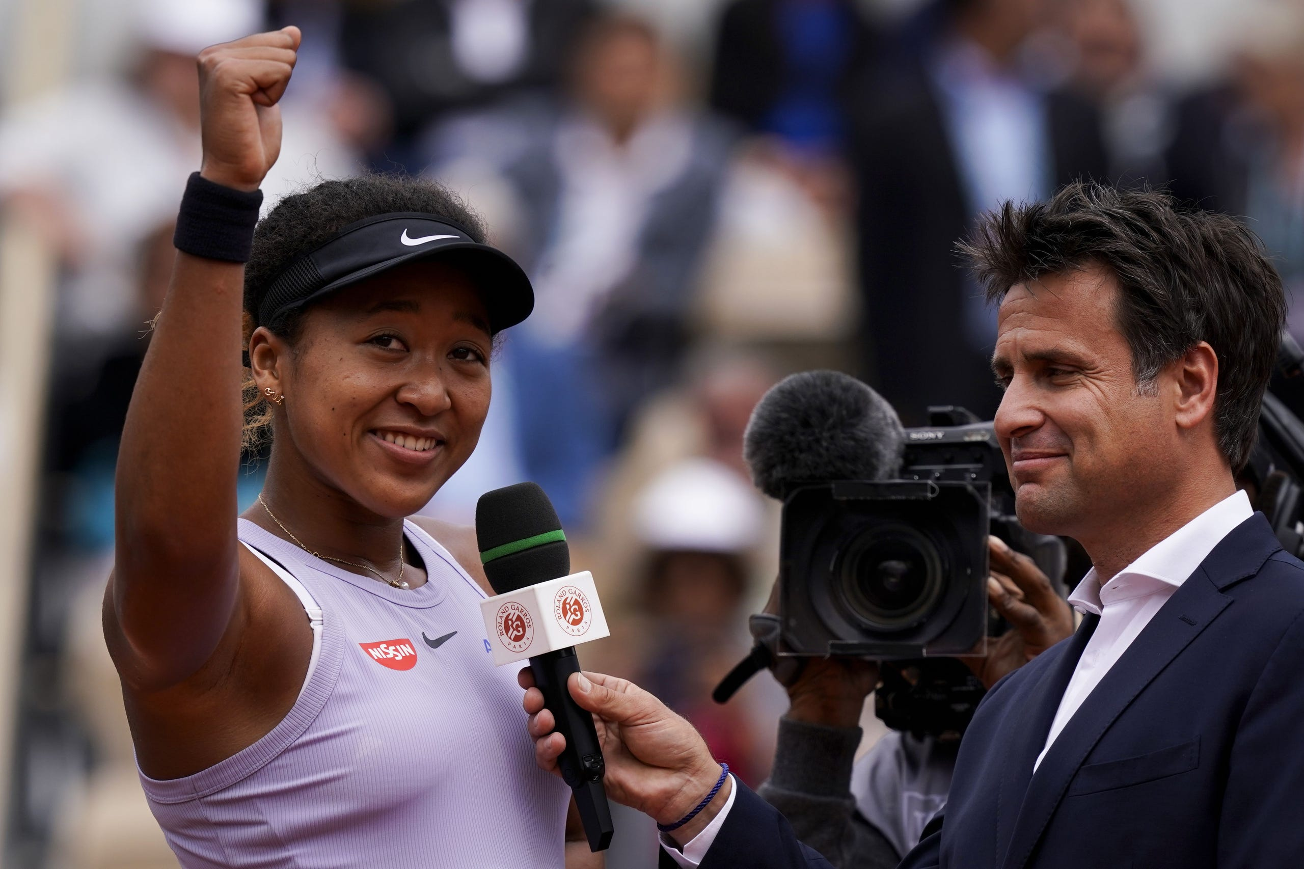 Naomi Osaka celebrates as she speaks with French former tennis player Fabrice Santoro, after winning against Belarus' Victoria Azarenka during their women's singles second round match on day five of The Roland Garros 2019 French Open tennis tournament in Paris on May 30, 2019.