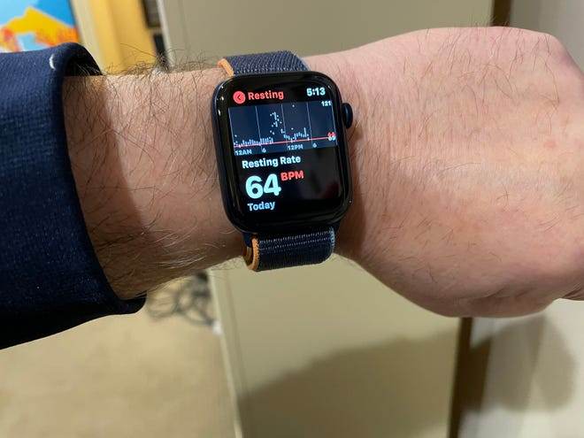 An Apple Watch shows a resting heart rate reading.