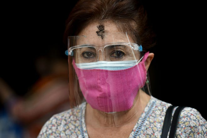 A Catholic faithful wears two face masks and a shield during the celebration of Ash Wednesday in Cali, Colombia, on Feb. 17, 2021. Ash Wednesday marks the Christian period of Lent, prior to the Holy Week.