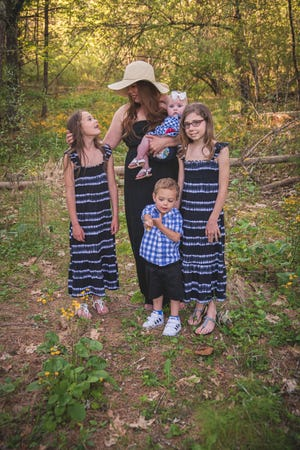 Meghan Hullinger (center) poses with her four children. The single mother from West Virginia has struggled to find adequate child care during the pandemic. Any stimulus money would be used for a babysitter to stay with her kids .