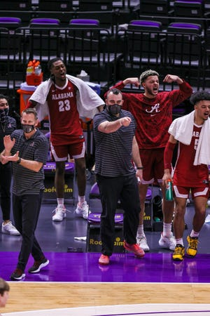Alabama coaches and players react from the bench to a play against LSU.
