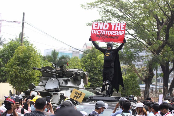 Protester on a vehicle parked next to an armored personnel carrier in Yangon, Myanmar, on Feb. 15, 2021.
