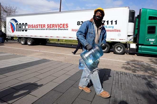 James White carries a bottle of donated water from a distribution site Thursday, Feb. 18, 2021, in Houston. Houston and several surrounding cities are under a boil water notice as many residents are still without running water in their homes.