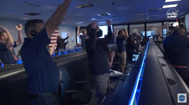 NASA officials celebrate as NASA's Mars Perseverance rover landed inside a crater on Feb. 18, 2021, after traveling in space for 204 days. Once the rover lands, it will embark on a two-year mission of searching for ancient microbial life.