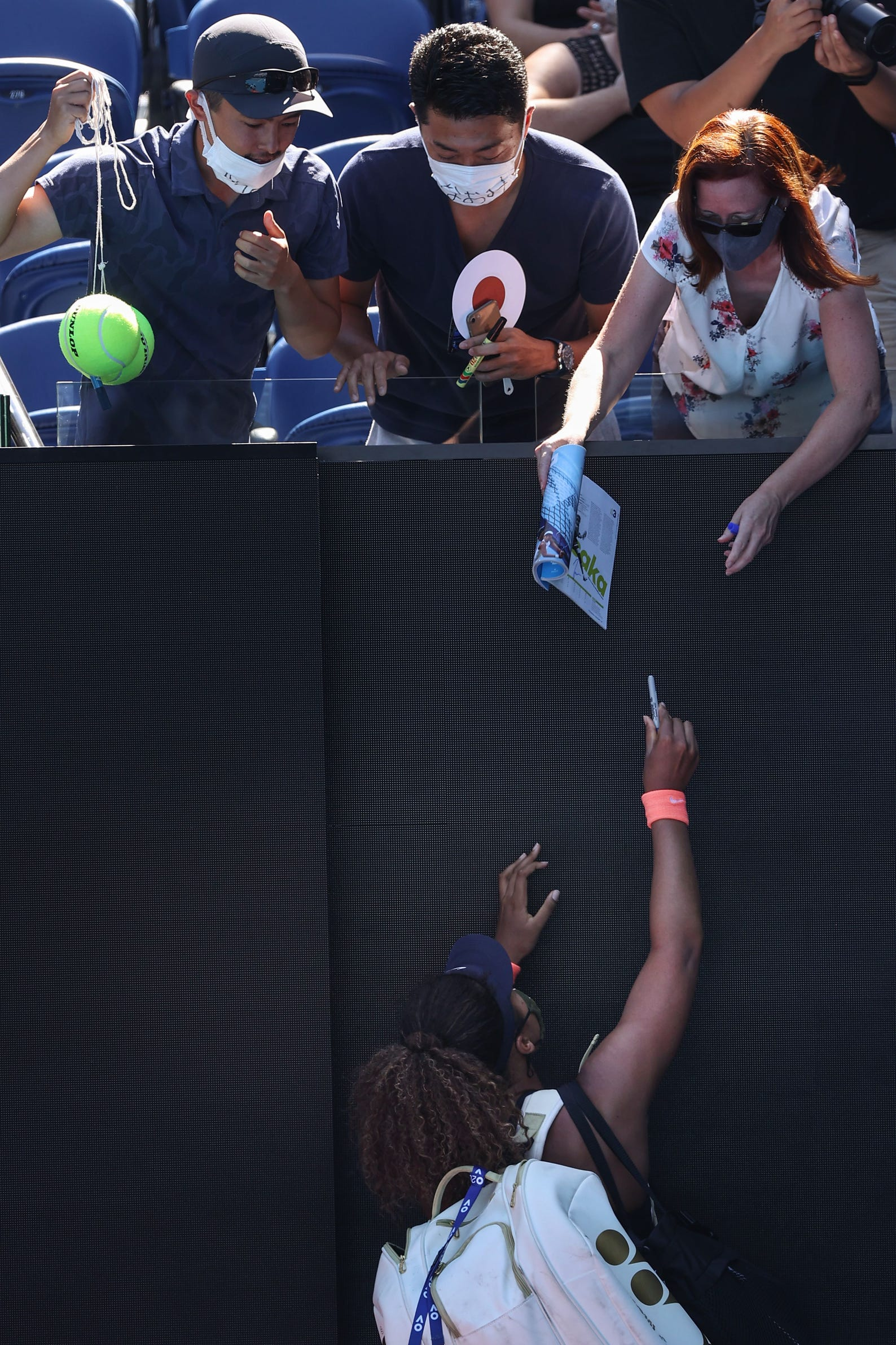 Japan's Naomi Osaka signs autographs for fans after beating Serena Williams of the US in their women's singles semi-final match on day eleven of the Australian Open tennis tournament in Melbourne on February 18, 2021.