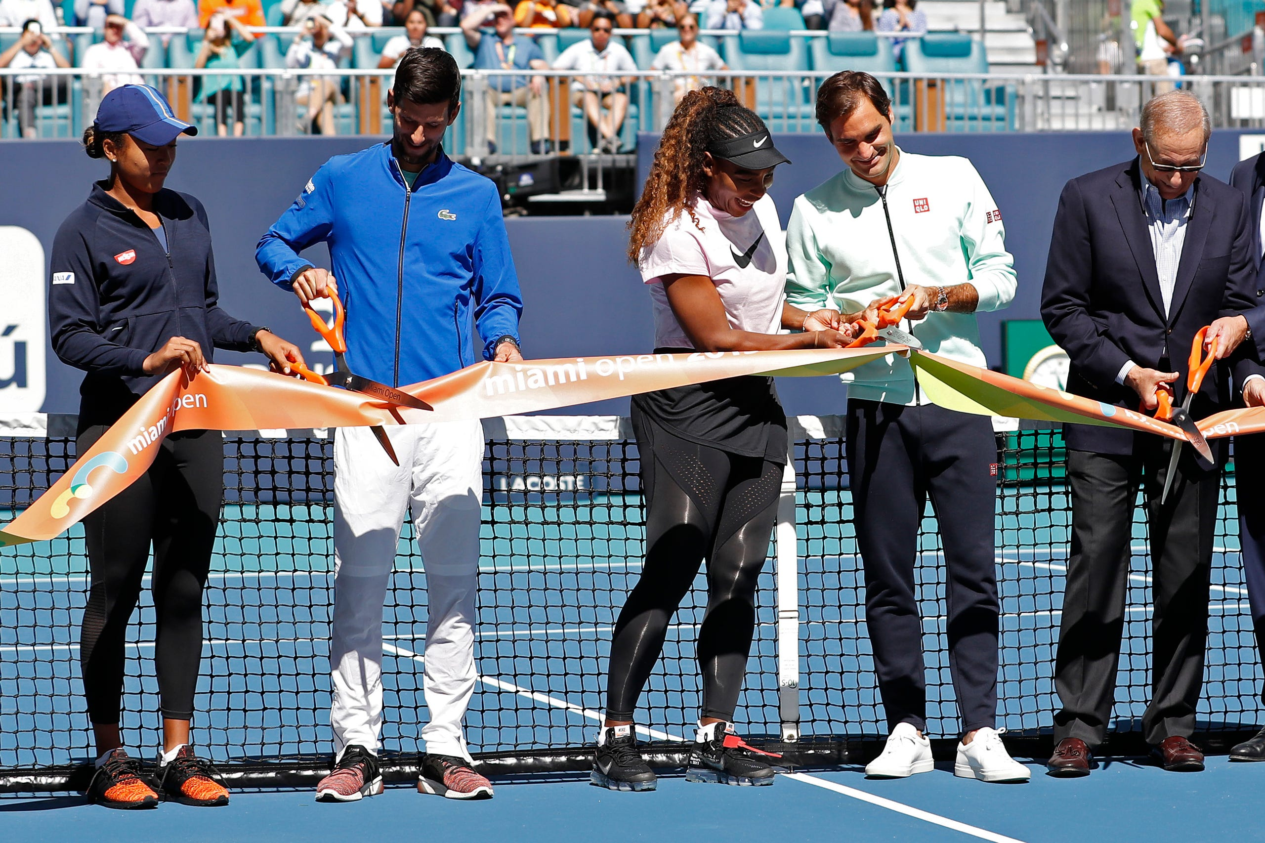 From left, Naomi Osaka of Japan, Novak Djokovic of Serbia, Serena Williams of the United States, and Roger Federer of Switzerland participate in a ribbon cutting ceremony on new stadium court at Hard Rock Stadium prior to play in the first round of the Miami Open at Miami Open Tennis Complex on March 20, 2019.