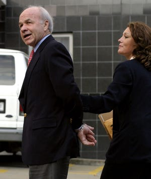 Former Enron CEO Ken Lay, left, is led into Federal Court by law enforcement officers in Houston after surrendering to the FBI in this July 8, 2004 file photo. Lay was a cheerleader for electric deregulation in Texas in the late 1990s. [AP Photo / Michael Stravato]