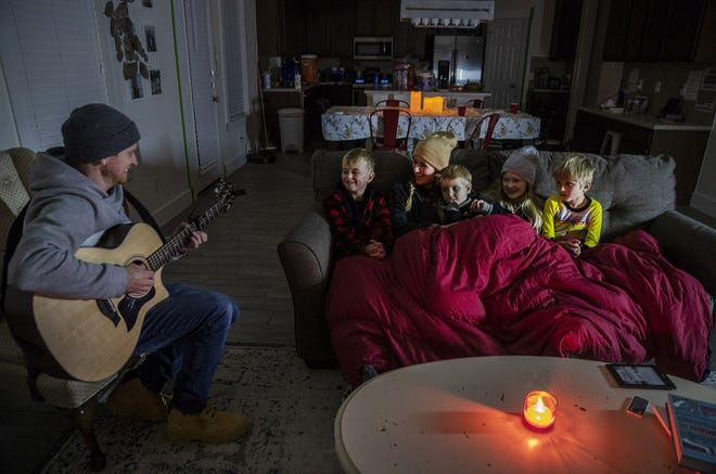 Brett Archibald entertains his family as they attempt to stay warm in their home the BlackHawk neighborhood in Pflugerville on Feb. 16.