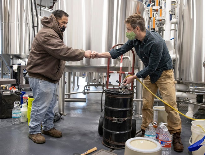 Will Jaquiss, right, the owner of Meanwhile Brewing Co., fills a container with water for Victor Perez on Friday during a citywide boil water notice. The brewery in Southeast Austin gave away all 4,000 gallons of their water to people in need on Thursday and Friday.