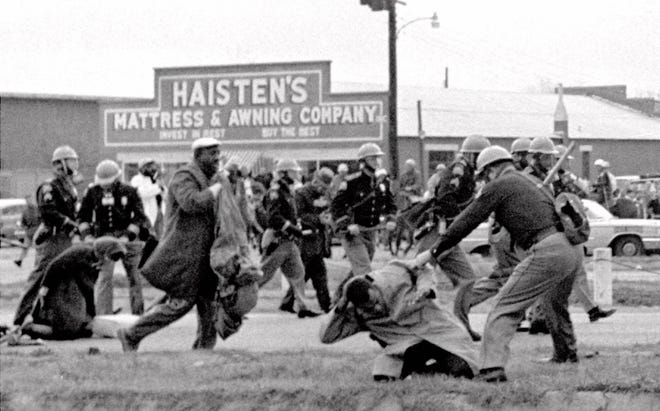 An Alabama state trooper swings a nightstick at John Lewis, the civil rights leader and former congressman who died in 2020, in this file photo taken March 7, 1965 in Selma, Ala.  [AP PHOTO/FILE]
