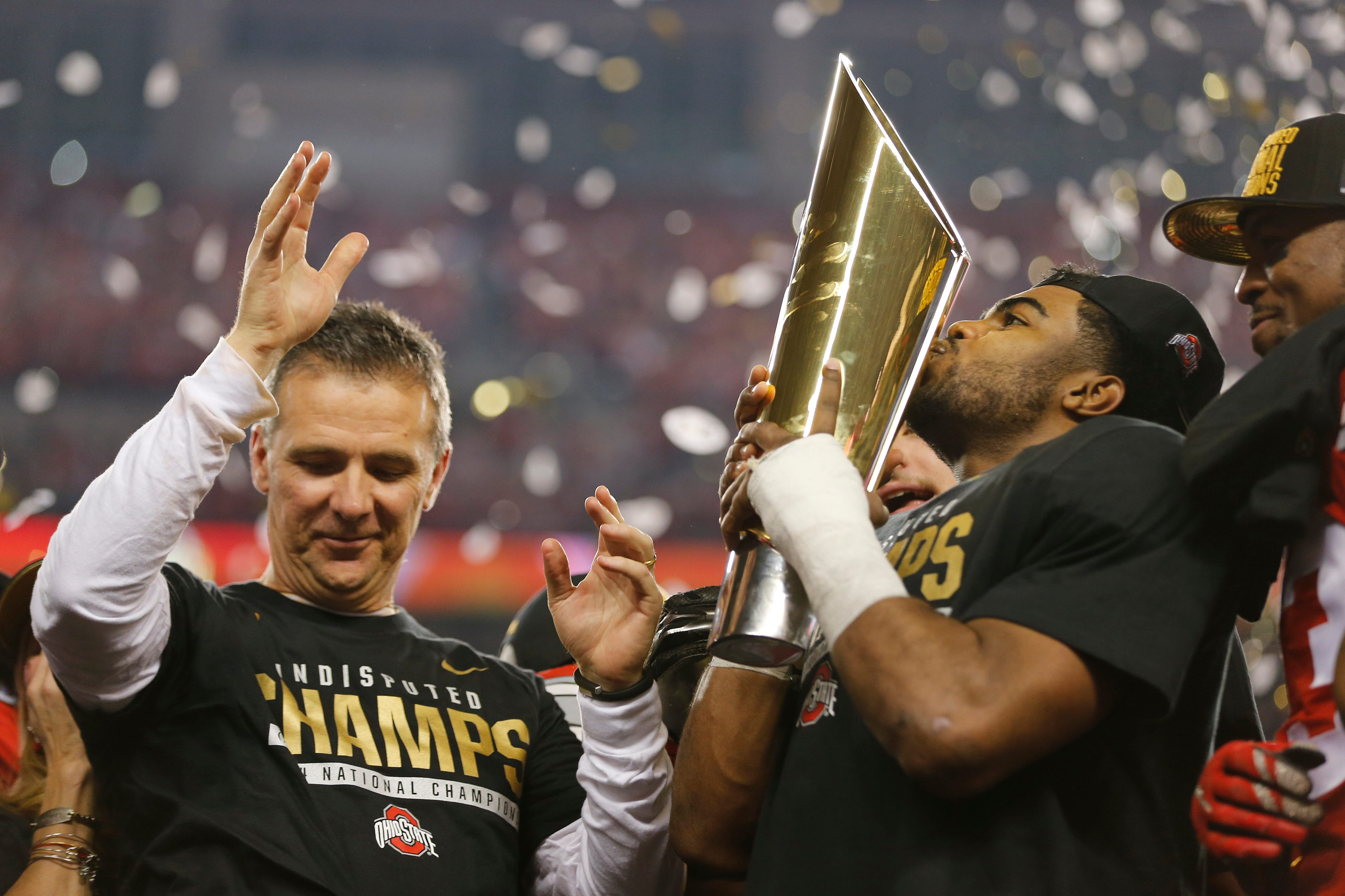 Ohio State running back Ezekiel Elliott kisses the championship trophy as Urban Meyer and the Buckeyes revel in the 42-20 walloping of Oregon in the 2014 national title game in Arlington, Texas.