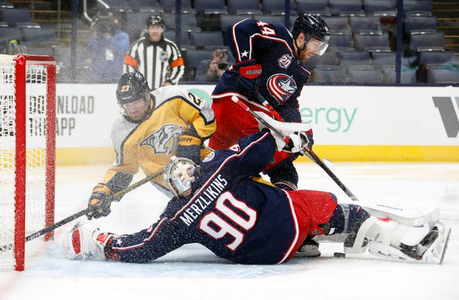 Blue Jackets goalie Elvis Merzlikins (90) makes a save against Nashville Predators right wing Rocco Grimaldi (23) during the second period Thursday night at Nationwide Arena. The Blue Jackets won 3-0 for Merzlikins' sixth career shutout.