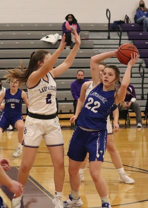 Cambridge junior Ziciah Gibson (22) looks for a team mate around a Martin Ferry defender during Thursday's Division III sectional final at Martins Ferry High School.