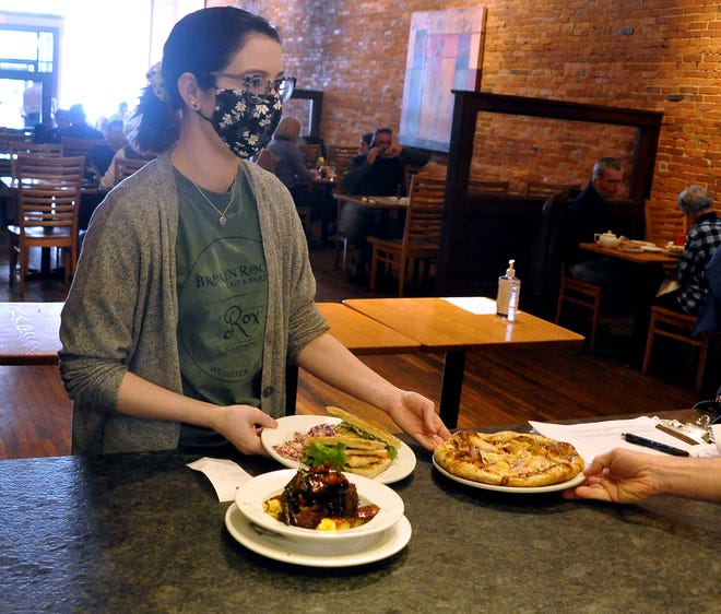 Kaitlyn Cox picks up orders recently to deliver to waiting customers in Broken Rocks in downtown Wooster.