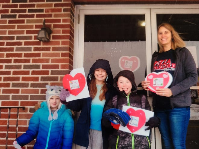 Paisley, Jerron and Peyton Scott of the Killbuck Church of Christ junior worship class present Pizza Parlor owner Jenny Wilcox with hearts to be displayed in her windows. The class made 55 hearts to display in Killbuck merchant windows during February to show love to the community.