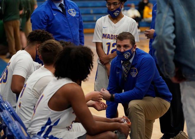 Madison head coach Erik Thompson talks to his team during a timeout Thursday against Sand Creek.