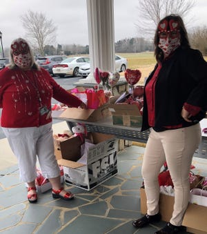Hospice of Davidson County volunteer Lucinda Amos picks up valentines to distribute from Hospice of Davidson County Volunteer Manager Hillary Bennett.